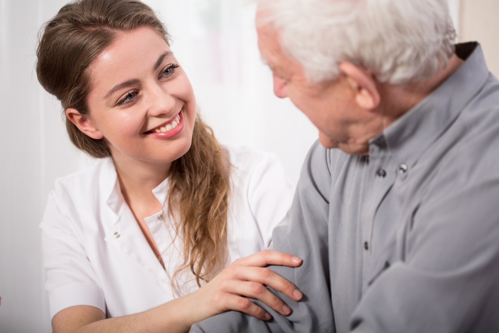 Picture of smiling nurse assisting senior man-1