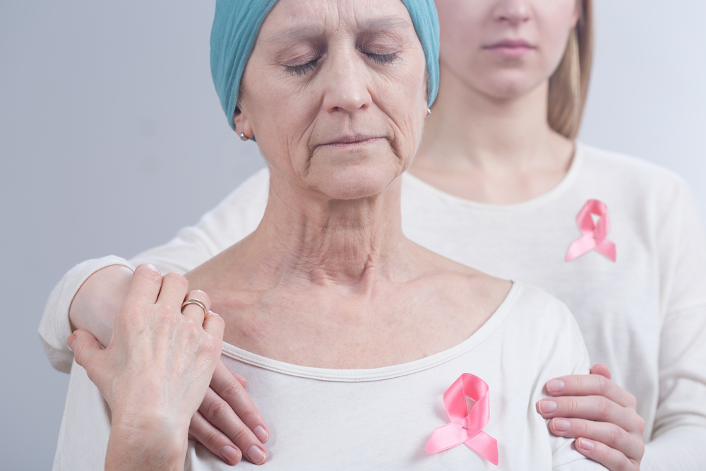 Cancer woman and young girl with pink ribbon, embracing