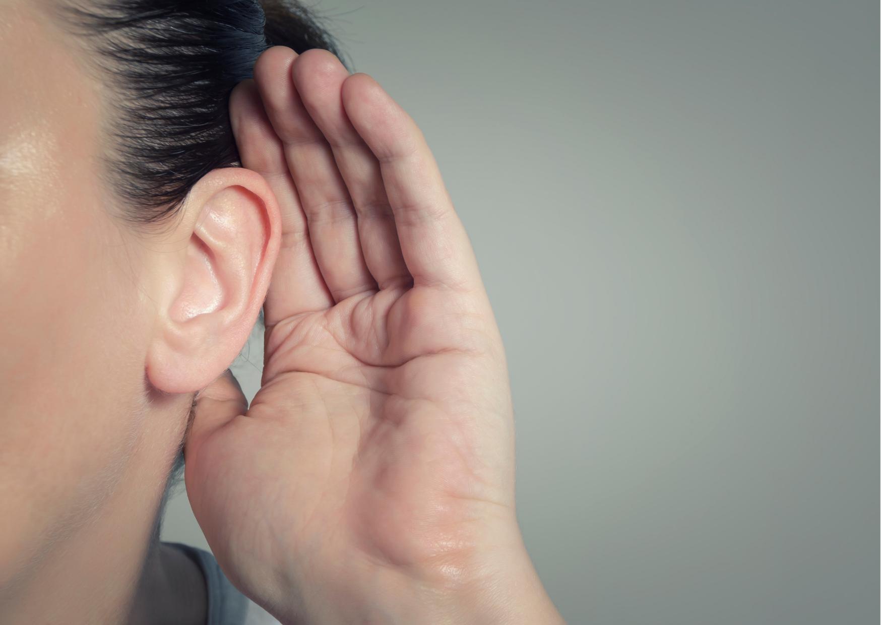 Mensch hält seine Hand ans Ohr um besser zu hören.