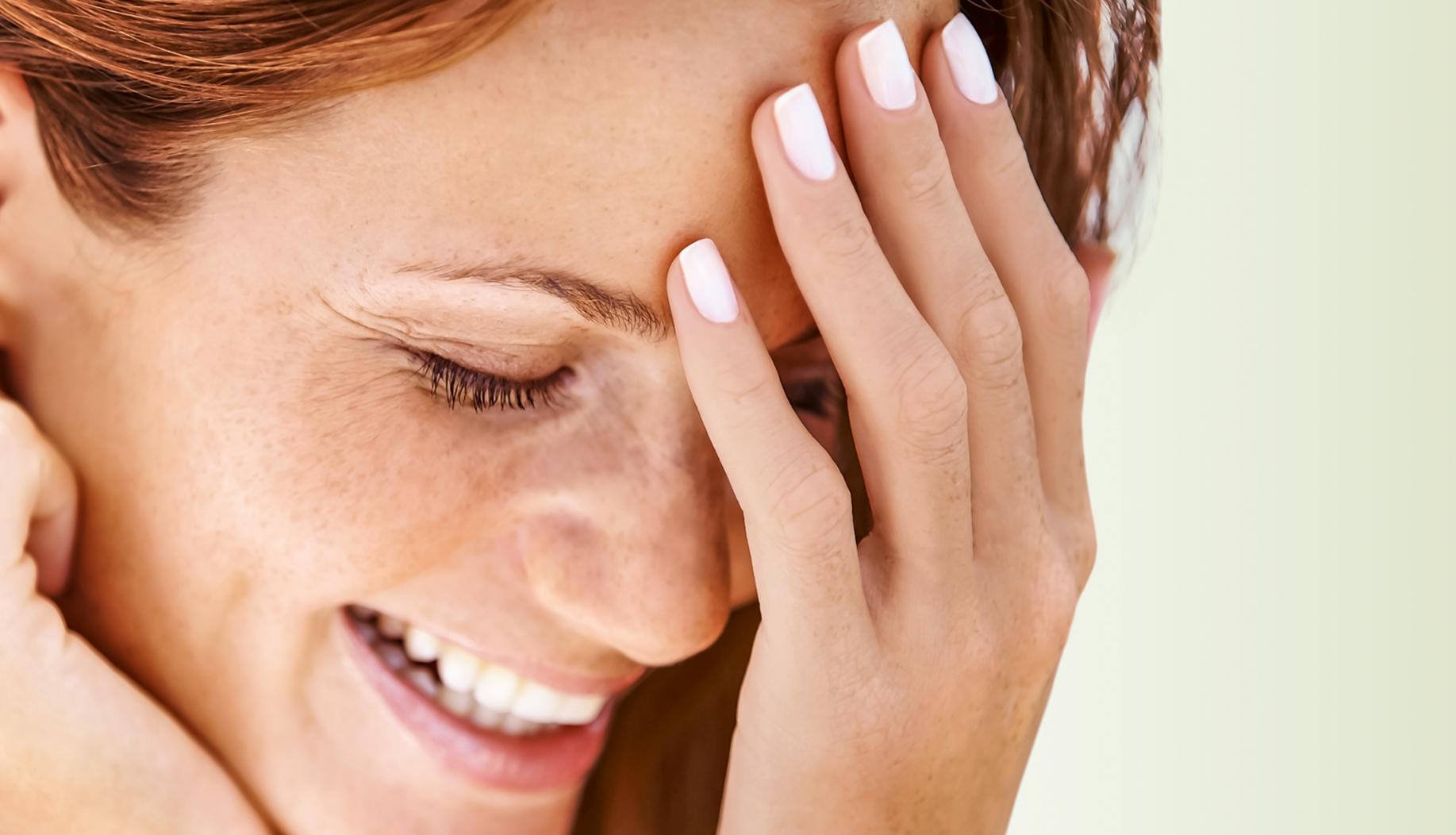Junge Frau lächelt und hält eine Hand vor das Gesicht.