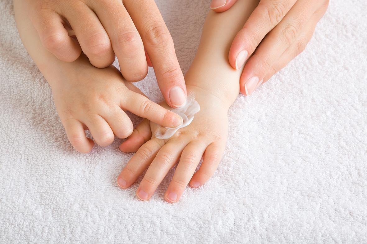 Hand einer erwachsenen Person hilft einem Kind beim Eincremen der Handobfläche.