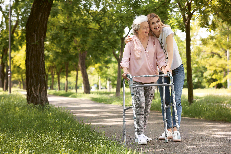 Seniorin läuft an Gehhilfe durch den grünen Park mit einer jungen Dame als Begleitung.